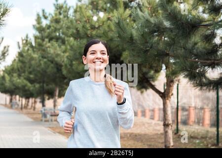 stile di vita sano. allegra donna attraente che corre in parco con alberi di pino al mattino Foto Stock