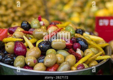 Un mucchio di olive in salamoia di diverse varietà. Mescolare con i peperoni caldi in una ciotola di metallo. Sfondo sfocato. Stile arabo. Il Vecchio Mercato, Gerusalemme. Foto Stock