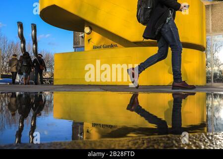Londra, Regno Unito. 1st Mar, 2020. I visitatori del Southbank Centre di Londra si riflettono nei pozzanghere della pioggia mentre camminano davanti ad una delle iconiche scale architettoniche brutali di colore giallo brillante del centro. La giornata a Londra ha visto un bel sole con cieli blu, in netto contrasto con la pioggia e la tempesta del sabato. Credito: Imageplotter/Alamy Live News