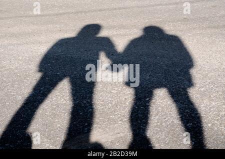 Serie di silhouette di giovani amanti. Serie 1. Ombra degli amanti mano in mano al tramonto. Un ragazzo e una giovane ragazza sono in piedi nelle vicinanze tenendo le mani. Sh Foto Stock