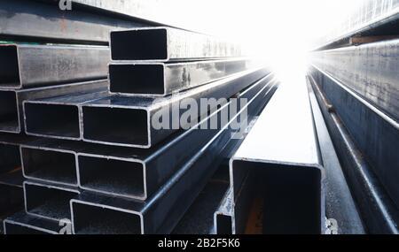 La pila di prodotti metallici laminati si trova in un magazzino, tubi in acciaio a sezione rettangolare, vista prospettica