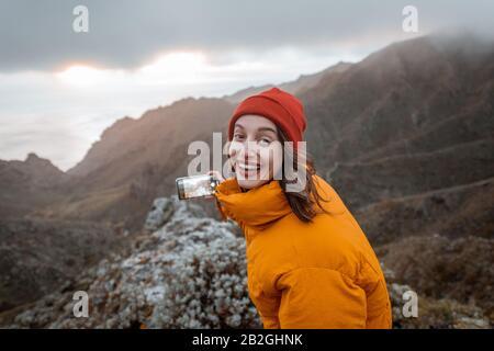 Ritratto di un giovane viaggiatore vestito di giacca luminosa e cappello godendo di un viaggio altamente in montagna, viaggiando sull'isola di Tenerife, Spagna Foto Stock