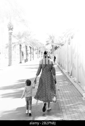 Madre e bambino camminano mano in mano lungo passerella costeggiata da palme in bianco e nero Foto Stock