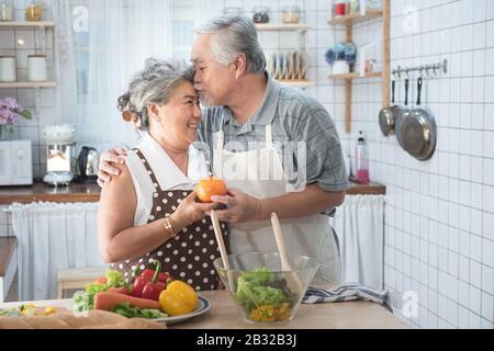 Coppia senior divertirsi in cucina con cibo sano - Persone In Pensione cucina pasto a casa con l'uomo e la donna preparare il pranzo con verdure bio - H.