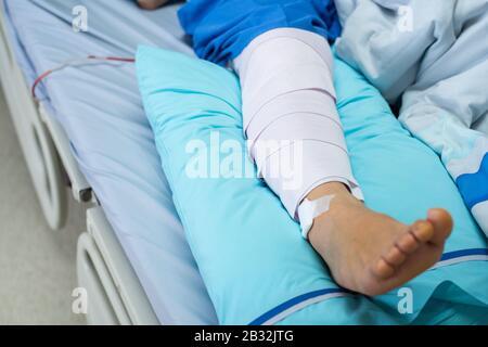 Pazienti asiatici anziani o anziani con braccio di compressione a bandera per sostenere lesioni al letto nell'ospedale del reparto infermieristico.