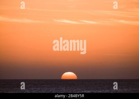 Classico tramonto tropicale o alba sul mare orizzonte con sole e acqua che si toccano insieme - arancio caldo cielo in background - destinazione viaggio paradiso concetto di vacanza Foto Stock