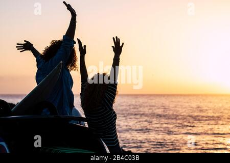 Felicità e concetto di successo con coppie di giovani amici godere il tramonto in vacanza vacanza estate - gioioso e persone in viaggio all'aperto attività di svago - oceano e sfondo del sole Foto Stock