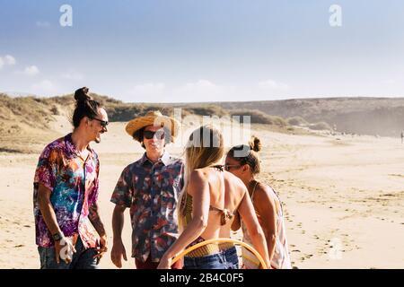 Gruppo di persone giovani amici godere e divertirsi in spiaggia - turismo e concetto turistico per vacanze estive - sole e belle uomini e donne insieme all'aperto in amicizia