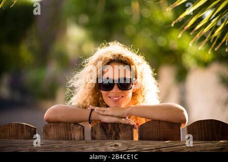 Ritratto di bella caucasica giovane bionda curly donna allegro guardando la fotocamera con luci del sole in background e defocused verde naturale sfondo esterno - felice età media signora concetto