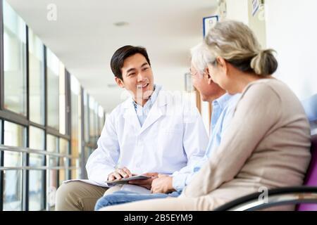 un giovane medico asiatico cordiale che parla con la vecchia coppia nel corridoio dell'ospedale