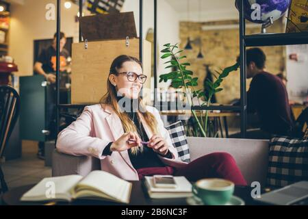 Sognando la signora graziosa che pensa alle idee seduta nel caffè, professione creativa. Tema moderno blogger femminile. Giovane donna con la penna in mano che pensa sopra