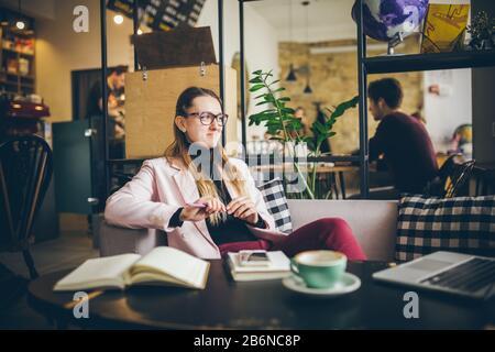 Bella donna caucasica sognando qualcosa mentre si siede con il computer in moderno caffè. Donne freelancer pensare a nuove idee durante il lavoro