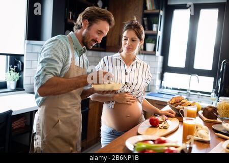 Ritratto di felice coppia giovane cucinare insieme nella cucina di casa.