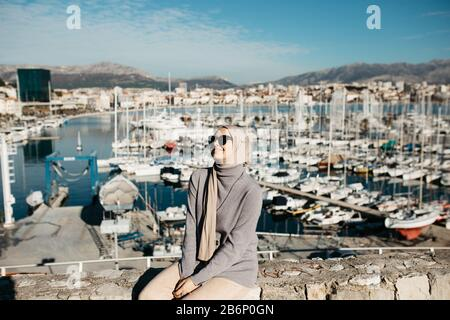 Ritratto di giovani donne musulmane europee con hijab seduto sulla spiaggia di pietra con mare e porto sullo sfondo. È felice e godendo del sole.