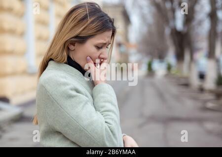 Depressa donna triste nel profilo quasi piangendo su una strada della città in Europa, guardando giù, piangendo a causa del suo tradimento ragazzo Foto Stock