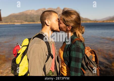 Vista laterale della coppia baciata di fronte al lago Foto Stock