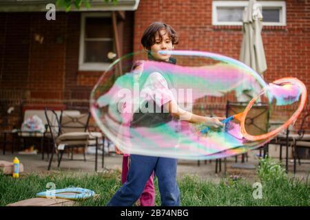 Un ragazzo e sua sorella giocano con gigantesche bolle di sapone nel cortile posteriore