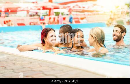 Amici felici che nuotano nella piscina del parco acquatico per le vacanze estive - giovani etniche diverse che si divertono a immergersi in acqua con il sole luce di schiena - Frien