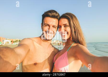 Felice coppia in viaggio facendo selfie con la spiaggia sullo sfondo - concetto di soleggiato estate colori e l'umore romantico - i giovani ridono e fanno em Foto Stock