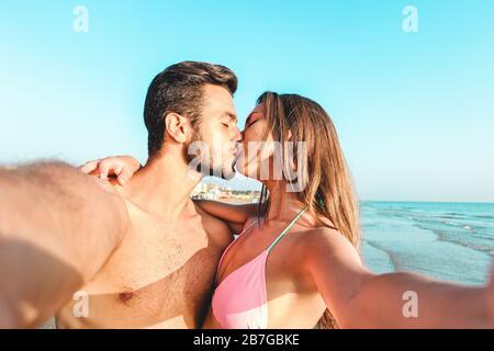 Felice coppia di viaggio facendo selfie con la spiaggia in background - concetto millennials ragazza e ragazzo in vacanza estiva - giovani persone che hanno Foto Stock