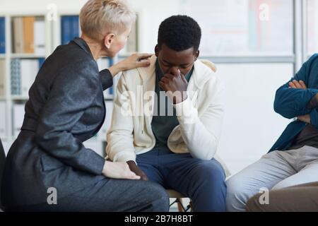 Ritratto di giovane afro-americano che piange mentre si siede sulla sedia in gruppo di sostegno cerchio, copia spazio