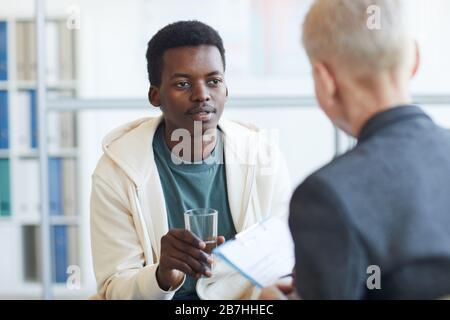 Ritratto del giovane afro-americano che tiene il bicchiere d'acqua durante la sessione di terapia, spazio copia