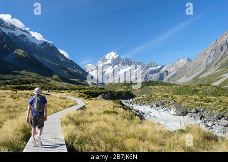 Uomo su sentiero con ghiacciai e montagne innevate, Hooker Track, Aoraki/Mount Cook National Park, South Island, Nuova Zelanda Foto Stock