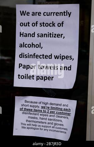 Avviso scritto di carenza e razionamento di forniture come coronavirus paura svuota scaffali presso farmacia locale Foto Stock