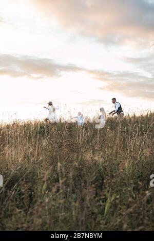 Buon padre di famiglia, madre e due figlie bambini che corrono e si divertono insieme sulla natura campo estivo al tramonto Foto Stock