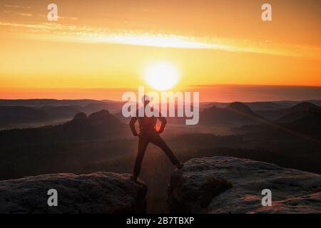 Uomo escursionismo silhouette in montagna, salto al tramonto. Escursionista maschile con bastoni da passeggio in cima al rischio di montagna Foto Stock