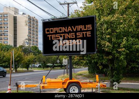 Segnale stradale digitale da una strada suburbana che dice Coronavirus Testing Site ahead Foto Stock