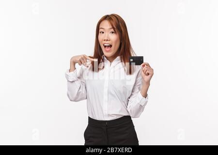 Ritratto di sciocco kawaii donna asiatica in camicia e gonna, puntando la carta di credito e sorridendo alla macchina fotografica, pubblicizzare il servizio bancario, l'acquisto online Foto Stock