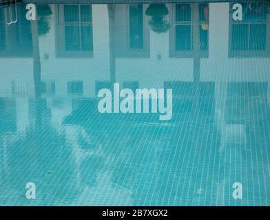 Case e palme riflessi vista in una piscina d'acqua piastrellata blu. Foto Stock