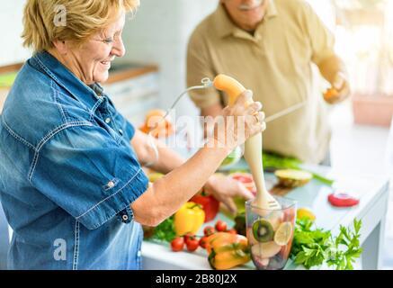 Coppia senior cucina sano pasto vegetariano con frutta e verdura insieme - persone anziane felici che si prendono cura di dieta e salute - Vegan e bio