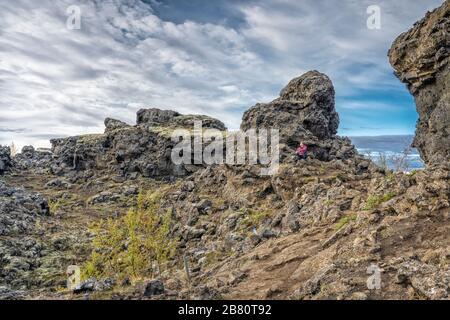 Donna che ammirava Dimmuborgir, un labirinto di enormi monoliti lavici, torri e caverna vicino al lago Myvatn nel nord dell'Islanda