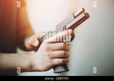 L'uomo sta tenendo una pistola nera airsoft, illuminata dalla luce, e ricaricarla.