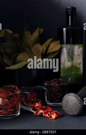 Peperoncini secchi a fette, spezie e pepe nero in ciotole di vetro. Mortaio di pietra e pestello, olio, rami di foglia di baia sullo sfondo. Composizione in