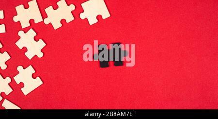 puzzle in legno bianco e nero su sfondo rosso primo piano vista dall'alto. outcast leader antisociale differiscono da altri bambini giocattolo educativo. Foto Stock