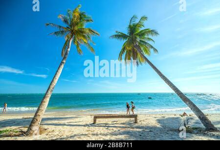 Un paio di turisti stranieri stanno facendo una piacevole passeggiata in una splendida baia nel pomeriggio estivo su una spiaggia tropicale a Mui NE, Vietnam