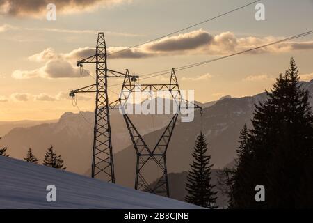 Torri ad alta tensione in montagna Alpi durante il tramonto. Foto Stock