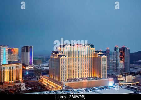 Vista aerea del Parigino Macao Hotel e degli edifici circostanti illuminati di notte. Cotai, Macao, Cina.