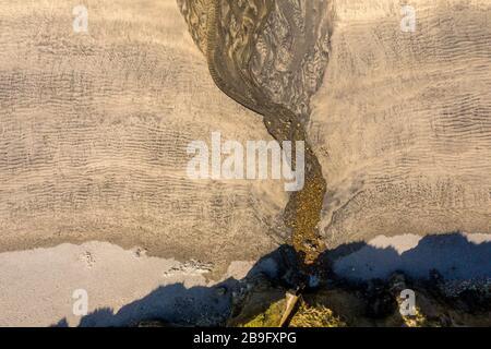 Immagine aerea dello scarico d'acqua delle scogliere e ruscello su sabbia dorata Foto Stock