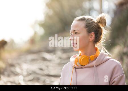 Ritratto di bella donna sportiva con felpa con cappuccio e cuffie durante la sessione di allenamento all'aperto.