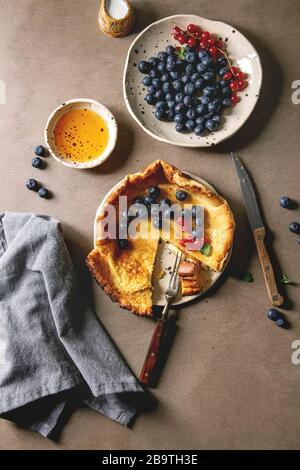 Iniziato mangiati freschi di forno olandese pancake bambino nella piastra ceramica servita con blackberry e rosse bacche Ribes, ciotola di miele, brocca di crema, taglio vintage