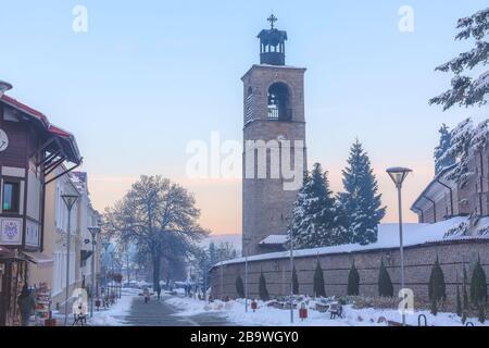 Bansko, Bulgaria - 6 dicembre 2019: Via Pirin nel centro storico, il campanile e le mura della chiesa di Sveta Troitsa