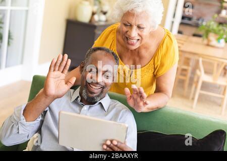 Coppia afroamericana utilizzando un tablet digitale in un canape Foto Stock