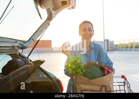 Giovane donna nel parcheggio, carico shopping in stivale di auto Foto Stock