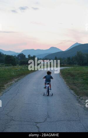 Little Boy Riding una bicicletta in montagna Foto Stock