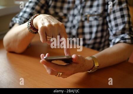 Donna anziana seduto al tavolo utilizzando il concetto di smartphone sempre online, connessione, shopping online, autoisolamento, tecnologia moderna per gli anziani