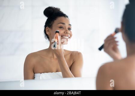 Bella donna africana tiene pennello applicare fondazione sulla faccia Foto Stock